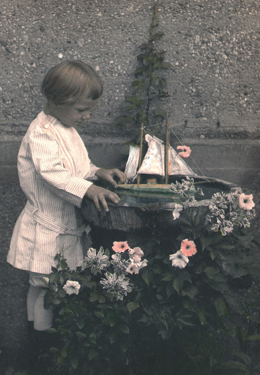 Detail: 1913: C.M. Shipman: American: his son, Mulford Cressey Shipman, (1910-1921) who died suddenly according to his obituary, plays with his toy sailboat in a birdbath: vintage platinum print with hand-coloring from memorial album: image: 21.8 x 15.2 cm: album support: 26.3 x 30.5 cm: from: PhotoSeed Archive