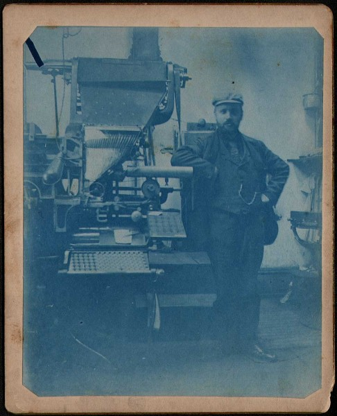 Man Standing Next to Linotype Machine